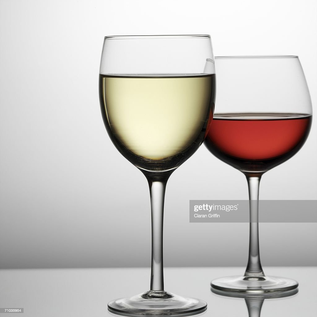 Close-up of a glass of white wine with a glass of red wine in the background : Stock Photo
