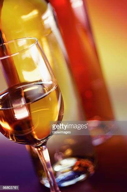 Close-up of a glass of wine with two wine bottles