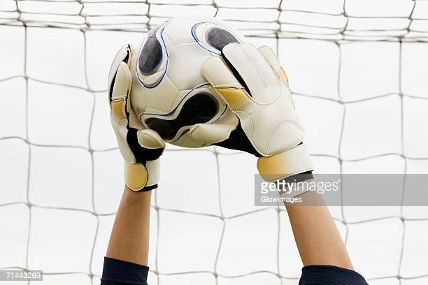 Close-up of a goalie's hands holding a soccer ball