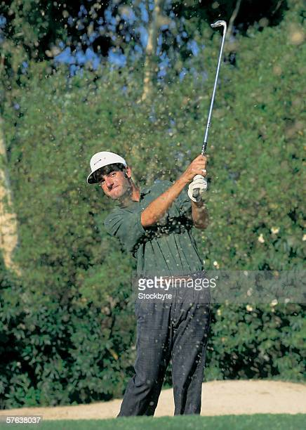 close-up of a golfer with the club raised after striking a shot - golf swing stock pictures, royalty-free photos & images