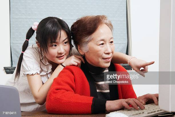 Close-up of a grandmother and her granddaughter using a computer
