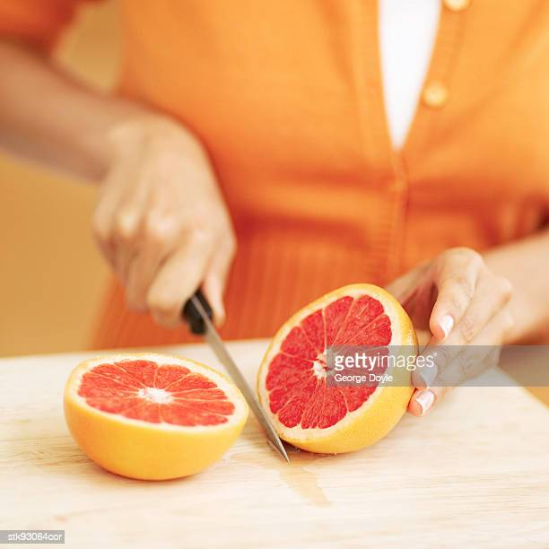close-up of a grape fruit being sliced in half