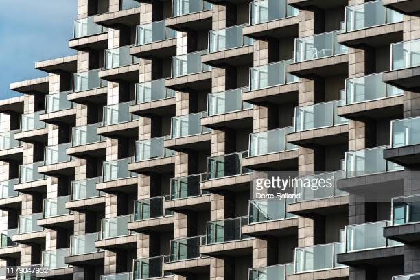 close-up of a grey facade with green tones glass balconies. clear blue sky in top left corner. - dorte fjalland stock pictures, royalty-free photos & images