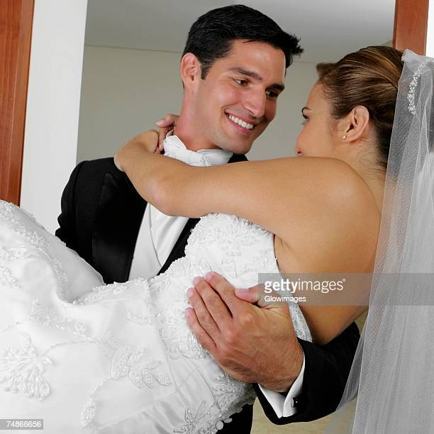Close-up of a groom carrying his bride and looking at each other