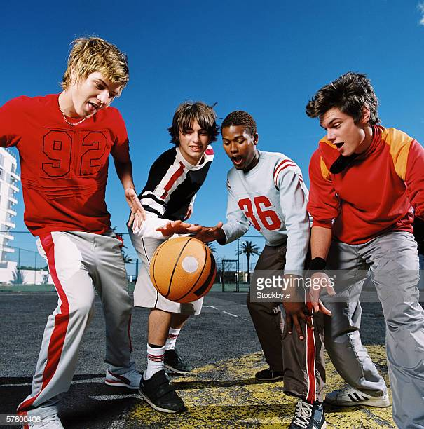 Close-up of a group of young men playing basketball