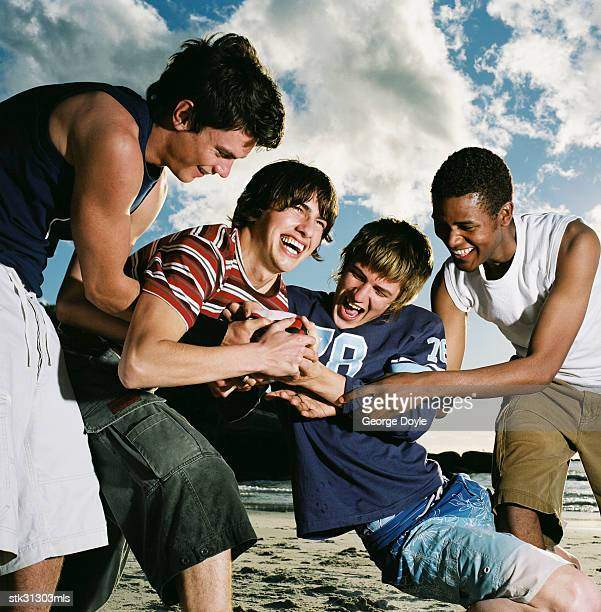 close-up of a group of young men smiling and tugging at a football on the beach