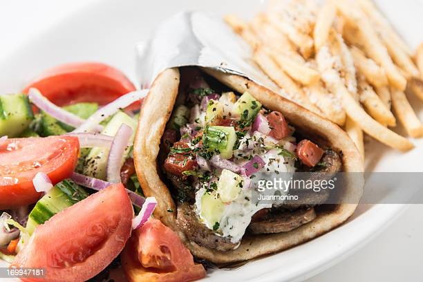 A close-up of a gyro pita sandwich with a salad and fries.