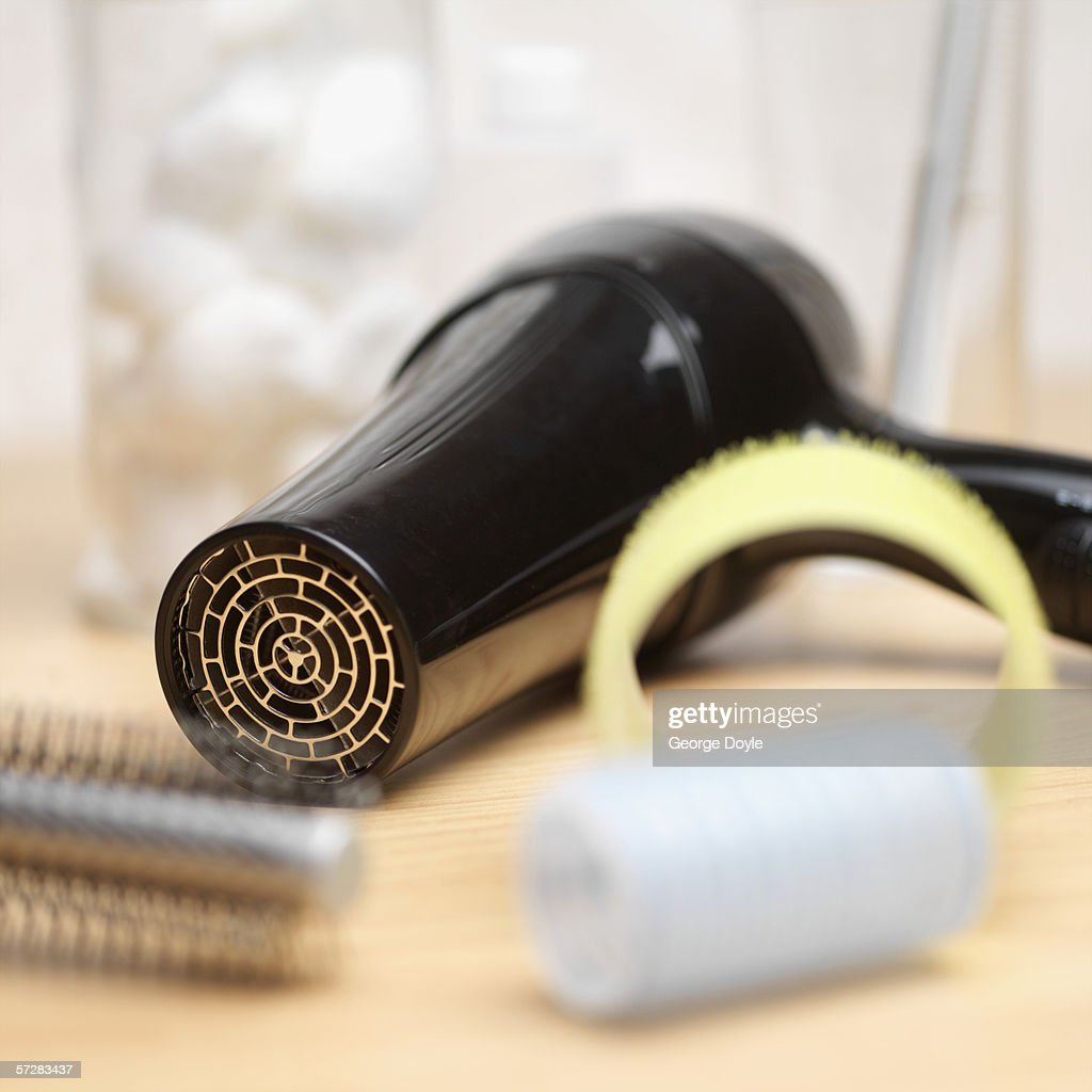 Close-up of a hair dryer, hairbrush and curlers : Stock Photo