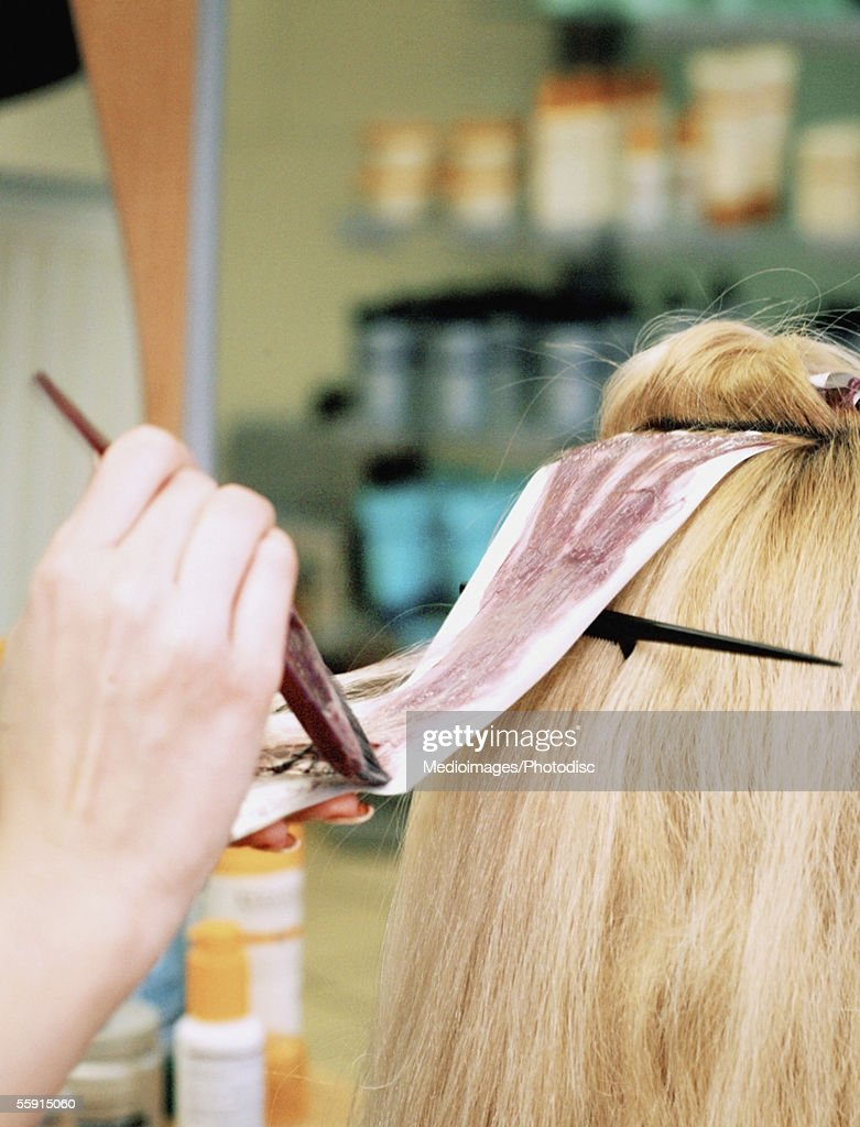 Close-up of a hairdresser's hand dyeing a mid adult woman's hair : Stock Photo