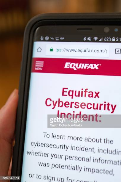 Closeup of a hand holding a cellphone open to the website of credit bureau Equifax showing information about a 2017 cybersecurity breach in which...
