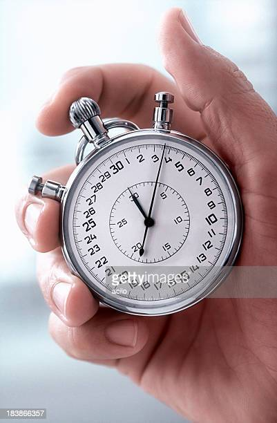 Close-up of a hand holding a classic silver stopwatch