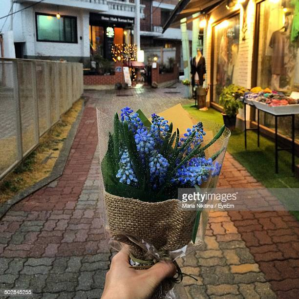 close-up of a hand holding bouquet on cobblestone pathway - nikitina stock pictures, royalty-free photos & images