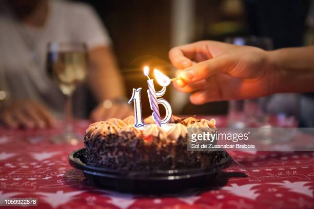 close-up of a hand turning on a candle on a chocolate and cream birthday cake with lighted candles and people gathered around it - quinceanera stock pictures, royalty-free photos & images