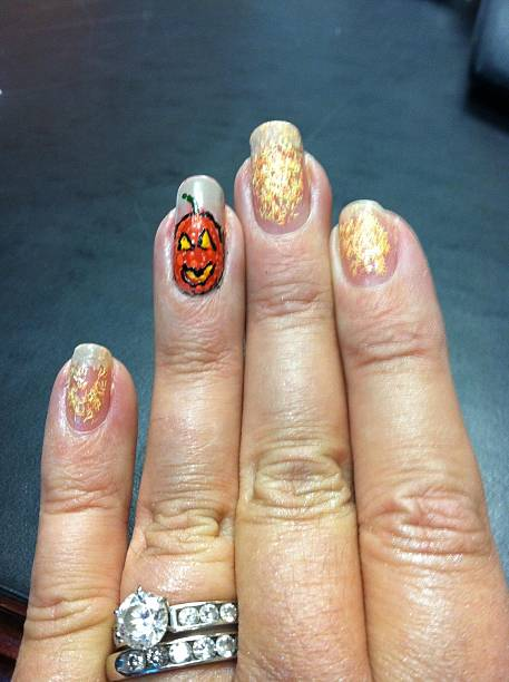 close-up of a hand with pumpkin design on finger nails - halloween nails stock pictures, royalty-free photos & images