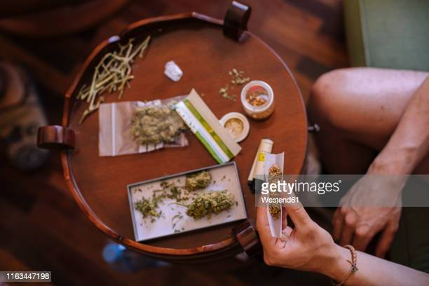 close-up of a hands rolling a joint of marijuana from above - personal accessory stock pictures, royalty-free photos & images