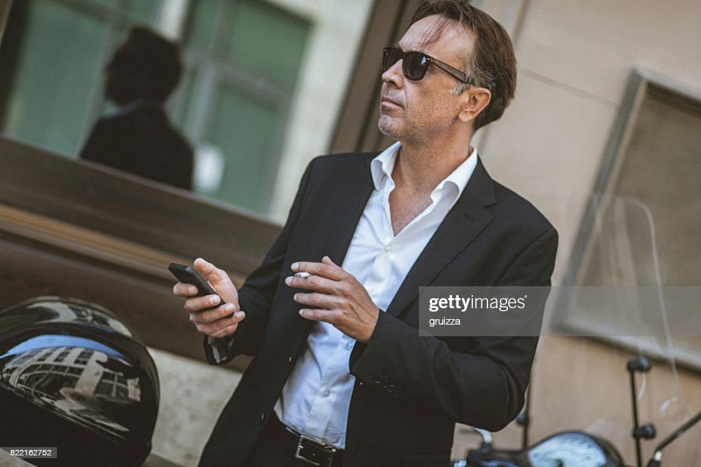 Close-up of a handsome, mature man using smart phone on the city street : Stock Photo