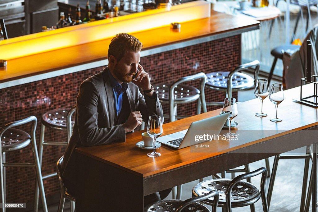 Nahaufnahme eines schönen jungen Geschäftsmann mit Handy und Laptop in einem Cafe : Stock-Foto