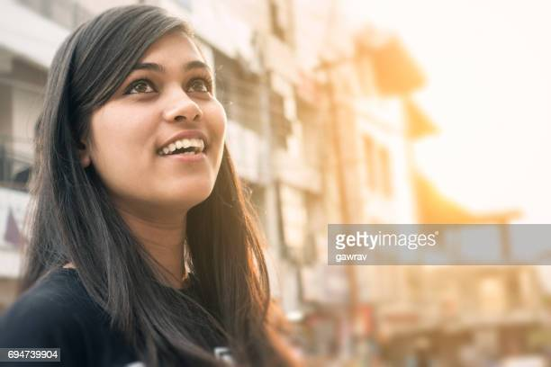 close-up of a happy asian girl on city street. - differential focus stock pictures, royalty-free photos & images