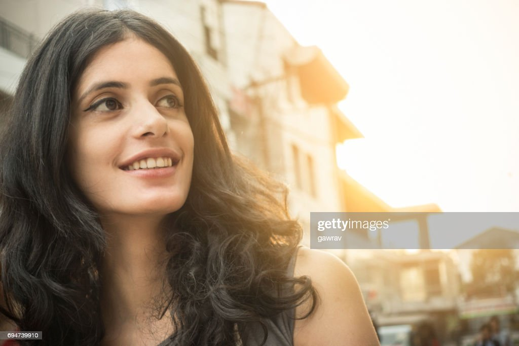 Close-up of a happy Asian girl on city street. : Stock Photo