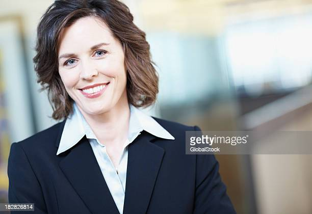 close-up of a happy mature businesswoman in office - mid length hair stock pictures, royalty-free photos & images