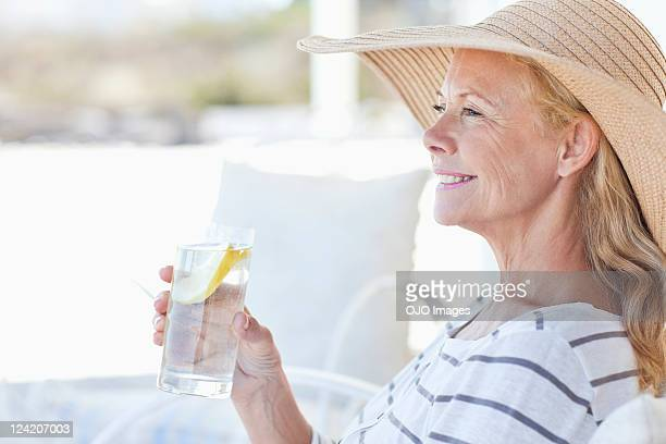 Close-up of a happy mature woman relaxing on porch with a glass of lemonade