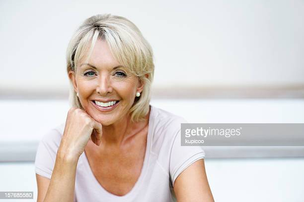 closeup of a happy mature woman with hand on chin - close to stock pictures, royalty-free photos & images