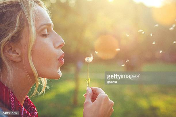 Close-up of a happy young blonde woman blowing dandelion