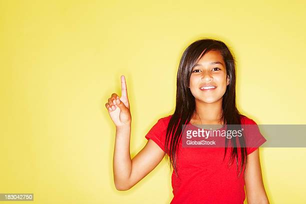 Closeup of a happy young girl pointing her finger up