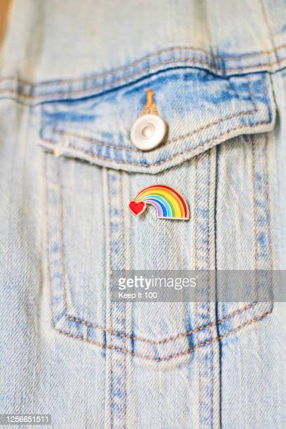 close-up of a heart rainbow badge on denim jacket pocket - brooch stock pictures, royalty-free photos & images