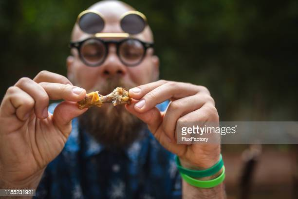 close-up of a hipster man eating friend chicken - chicken wings stock pictures, royalty-free photos & images