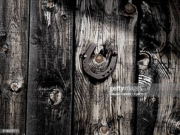 Close-up Of A Horseshoe Hanging On Wooden Wall