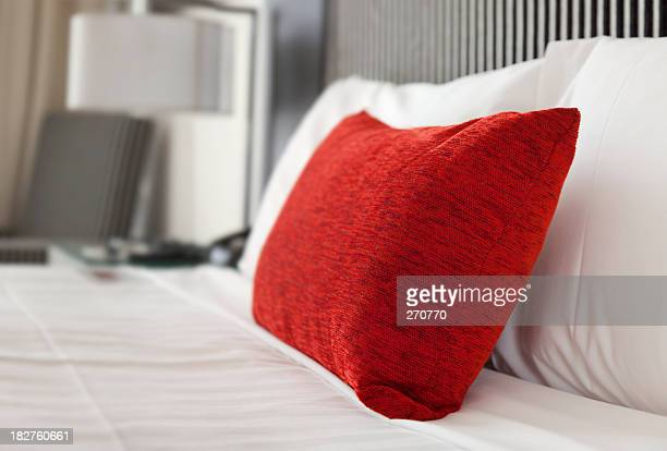 Close-up of a hotel bed with white sheets and one red pillow
