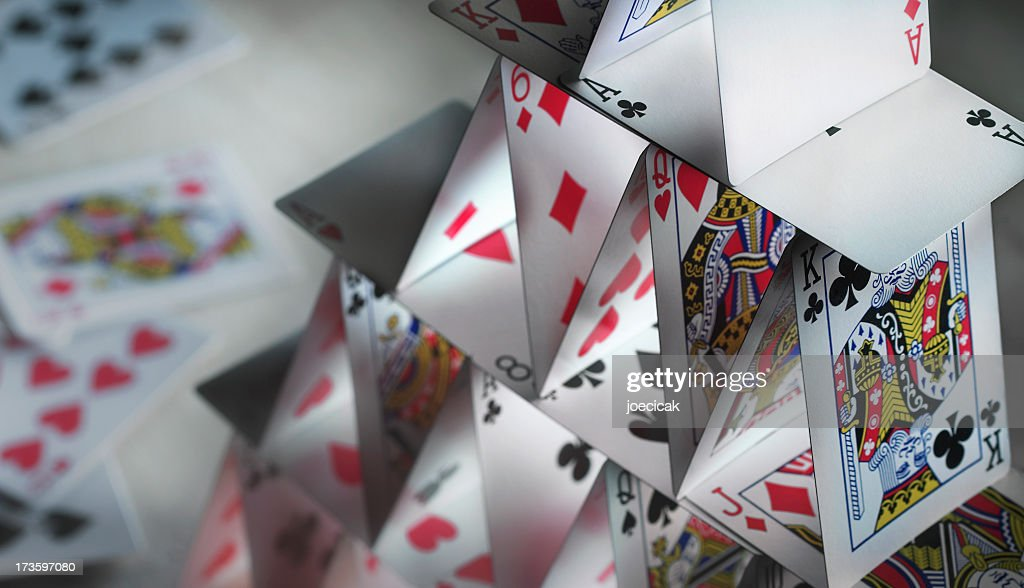 Close-up of a house of cards with spare cards in the back : Stock Photo