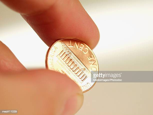 Close-up of a human hand holding a one cent coin