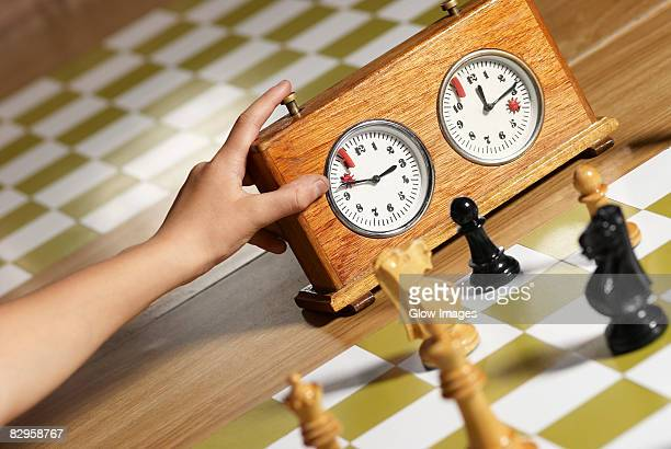 Close-up of a human hand pushing button of a chess clock