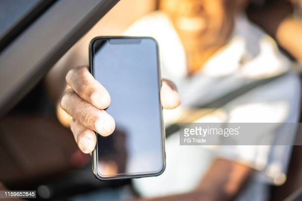 close-up of a human hand showing a phone screen - black hand holding phone stock pictures, royalty-free photos & images