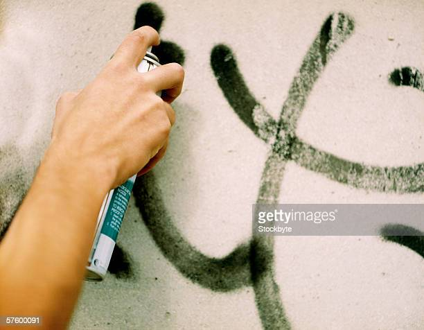 Close-up of a human hand spraying paint on a wall