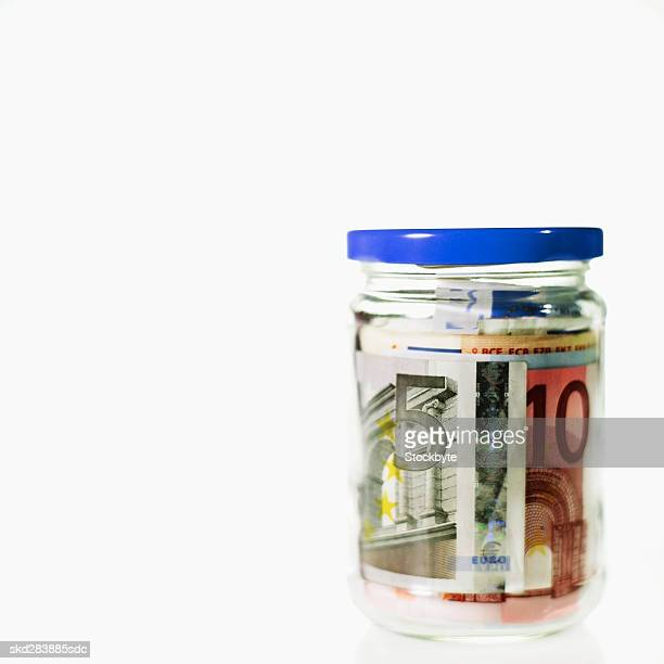 close-up of a jar containing euro bank notes - five euro banknote stock photos and pictures