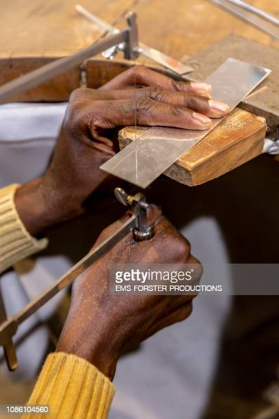 close-up of a jeweler sawing metal plate in his goldsmith store - fugitive stock pictures, royalty-free photos & images