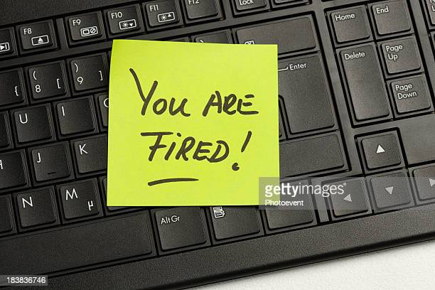 A close-up of a keyboard with a note saying you are fired