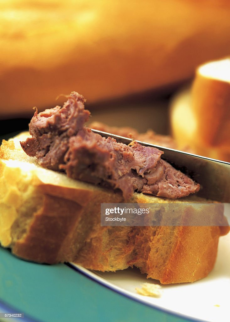 close-up of a knife spreading meat on a slice of bread : Stock Photo