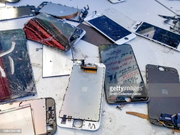 Closeup of a large number of broken cellphones including cracked cellphone screens with exposed wiring on a white surface suggesting E Waste...