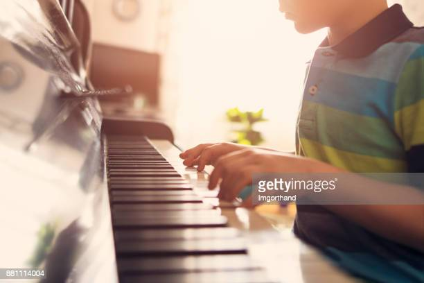 Closeup of a little boy playing piano