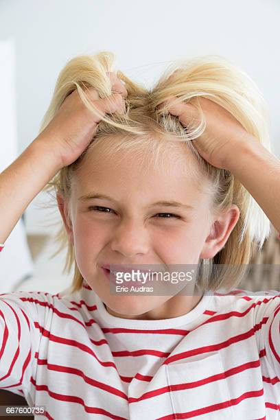 Close-up of a little girl scratching hair