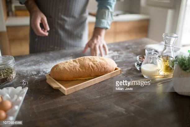 Close-up of a loaf of bread in front of man