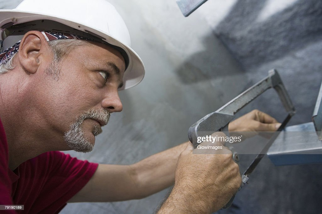 Close-up of a male construction worker cutting a metal sheet with a saw : Stock Photo