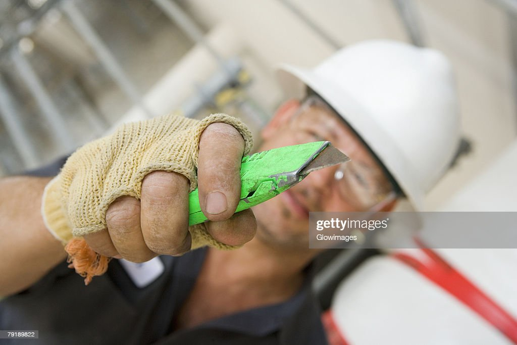 Close-up of a male construction worker holding a cutting tool : Foto de stock