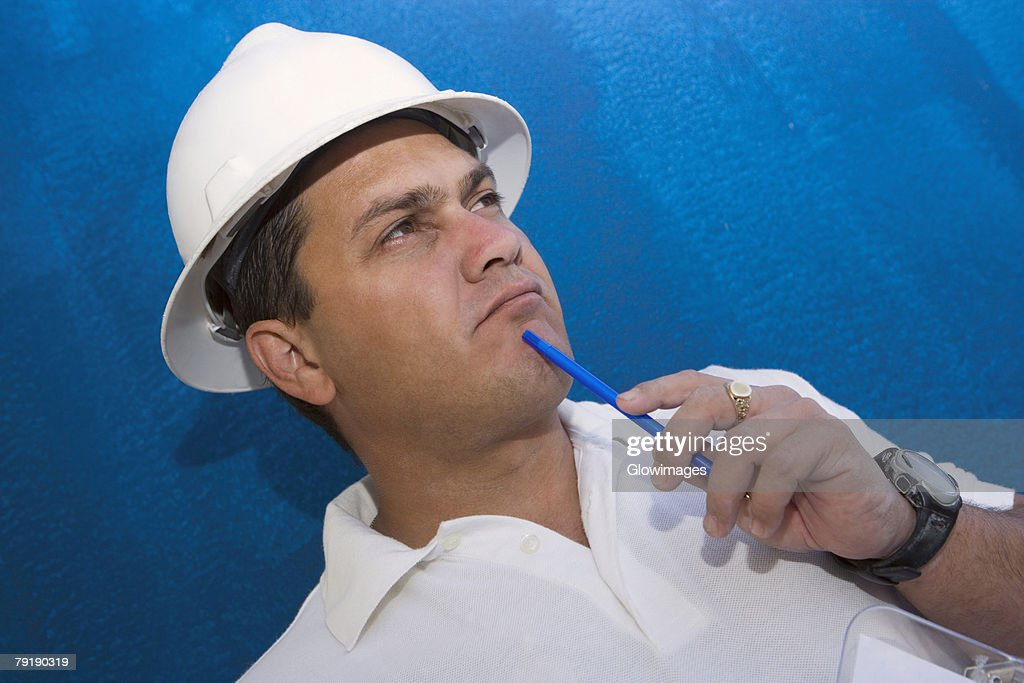 Close-up of a male construction worker holding a pen and thinking : Foto de stock