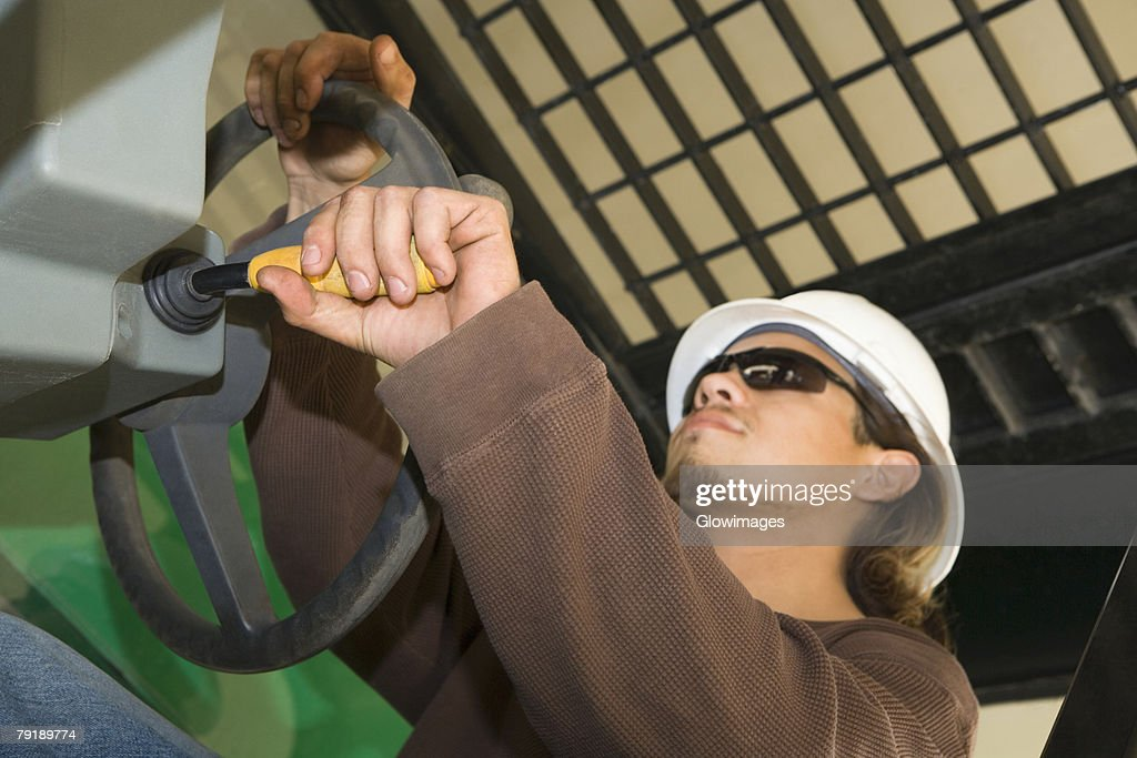 Close-up of a male construction worker holding a steering wheel : Foto de stock