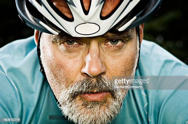 Closeup of a male cyclists face with grey beard and helmet